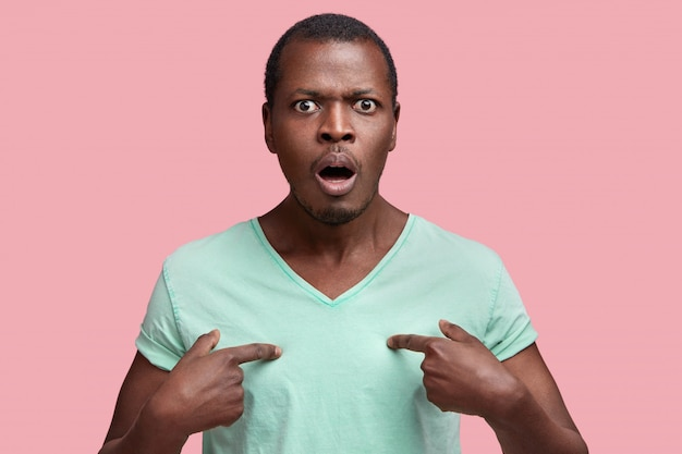 Displeased annoyed african american male model indicates at t shirt for your design or logo, frowns face and being dissatisfied with something, isolated over pink Free Photo