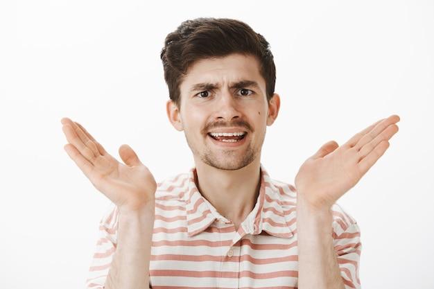 口ひげのある不機嫌な普通の白人男性、顔の近くで手のひらを上げて主張し、不機嫌でイライラしている、灰色の壁越しにナンセンスを聞く 無料写真