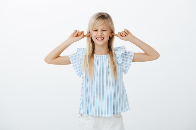 Недовольный раздраженный маленький ребенок со светлыми волосами в синей блузке, закрывает уши указательными пальцами и гримасничает, слышит раздражающий звук, стоит над серой стеной Бесплатные Фотографии