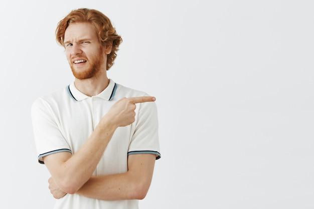 Ragazzo rosso barbuto scontento in posa contro il muro bianco Foto Gratuite