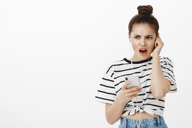 Ragazza lamentosa scontenta che sembra delusa, ascolta musica orribile o podcast in auricolari, tenendo il telefono cellulare Foto Gratuite