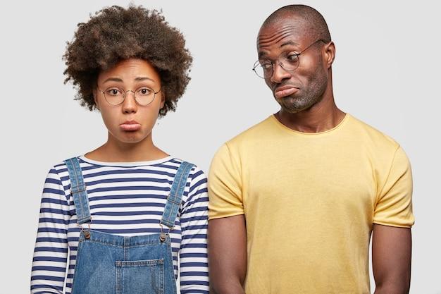 不機嫌なカップルは下唇を曲げ、休日を台無しにしたように不幸な表情で見て、カジュアルな服装をしています 無料写真