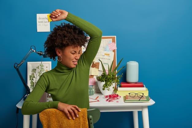 不機嫌な巻き毛の女性は、脇の下の下で不快な臭いがし、緑のタートルネックを着て、コワーキングスペースの上に座って、自分のキャビネットでの検査セッションの準備をし、疲れを感じます。 無料写真