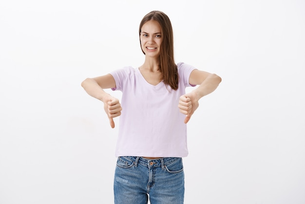 Displeased dissatisfied attractive young female customer in blouse and jeans showing thumbs down smiling awkwardly while giving negative feedback and rejection bad idea over white wall Free Photo