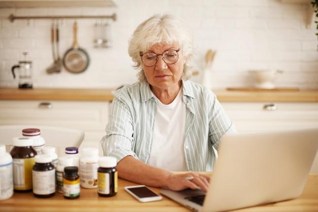 Недовольная пожилая европейская пенсионерка в круглых очках сидит на кухне, с презрением смотрит на бутылки с пищевыми добавками и набирает сердитый негативный отзыв на веб-сайте с помощью ноутбука Бесплатные Фотографии