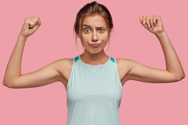 不機嫌なヨーロッパの女の子は顔をしかめ、彼女の筋肉を見せたいように手を上げます 無料写真