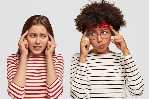 Le ragazze frustrate e scontente tengono l'indice sulle tempie, cercano di ricordare le informazioni in mente Foto Gratuite