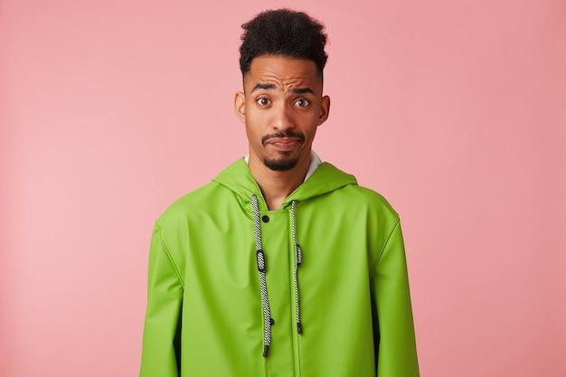 Scontento bel ragazzo dalla pelle scura in impermeabile verde, alzando il sopracciglio con aria interrogativa, dubbi e guarda la telecamera si leva in piedi su sfondo rosa. Foto Gratuite
