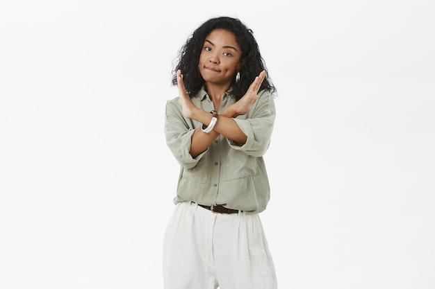 Femmina afroamericana intensa dispiaciuta con l'acconciatura riccia che increspa le labbra che fanno croce con le braccia Foto Gratuite