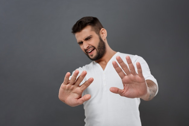 Displeased man refusing, stretching hands  over grey wall Free Photo