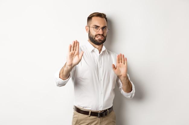 Uomo scontento che rifiuta qualcosa di inquietante, mostra il segnale di stop e rifiuta, rabbrividisce per l'avversione Foto Gratuite