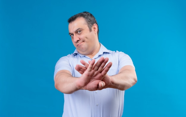 Displeased middle age man in blue vertical striped shirt raising hands in rejection on a blue space Free Photo