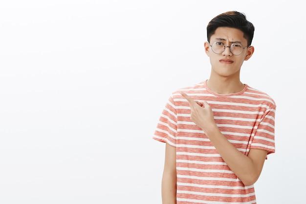 Studente maschio asiatico attraente giovane intelligente dispiaciuto in occhiali e maglietta che alza il sopracciglio nel disprezzo e nel dubbio che increspa le labbra dall'antipatia che punta all'indietro o lasciato in discussione Foto Gratuite