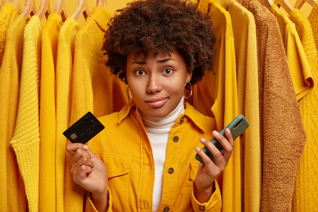 Displeased unaware woman with curly hairstyle, unable to pay all sum of money for clothes, holds plastic card and modern mobile phone, poses against plain yellow jumpers on hangers. Free Photo