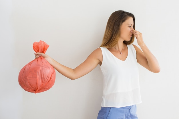Displeased woman holding garbage bag Free Photo