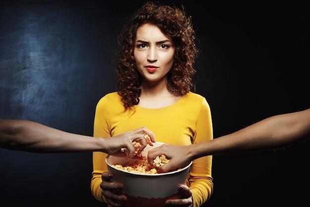 Secchio dispiaciuto del popcorn della tenuta della donna in mani che sembrano diritte Foto Gratuite