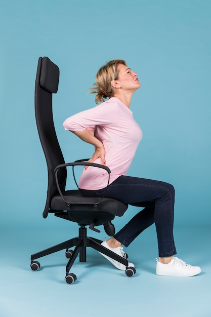 Displeased woman sitting in chair having backache on blue backdrop Premium Photo
