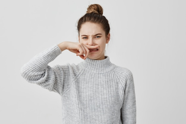 Displeased woman wearing casual closing nose with index finger looking with disgust
