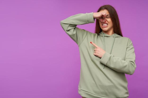 紫色の壁に隔離された悪臭を避けようとしている間、彼女の顔を顔をゆがめ、上げられた手で鼻を閉じる不機嫌な若い魅力的な長い髪のブルネットの女性 無料写真