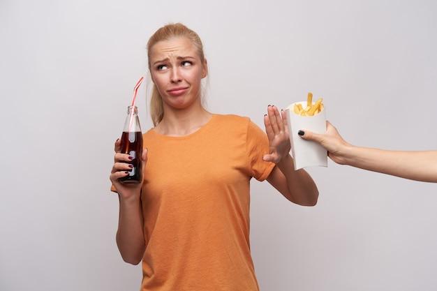 Недовольная молодая блондинка с непринужденной прической смотрит в сторону с надутыми губами и хмурится с поднятой ладонью, пьет газировку и отказывается есть картофель фри, изолированные на белом фоне Бесплатные Фотографии