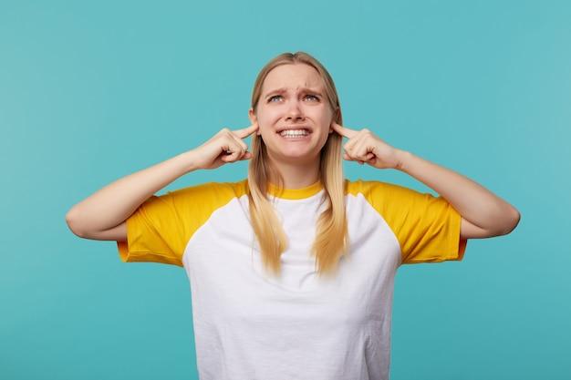 不快な若い青い目の金髪の女性は、大きな音を避けようとしている間、彼女の耳に人差し指を挿入し、青い背景の上に孤立した彼女の顔を不満に顔をゆがめます 無料写真
