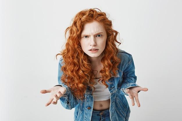 容赦なく身振りで示すカメラにストレッチする不機嫌な若いセクシーな女の子。 無料写真