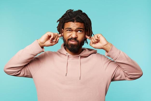 青い背景の上に立って、大きな音を避けようとしている間、彼の顔を顔をゆがめ、耳を覆っているひげを持つ不機嫌な若いハンサムな黒髪の男性 無料写真