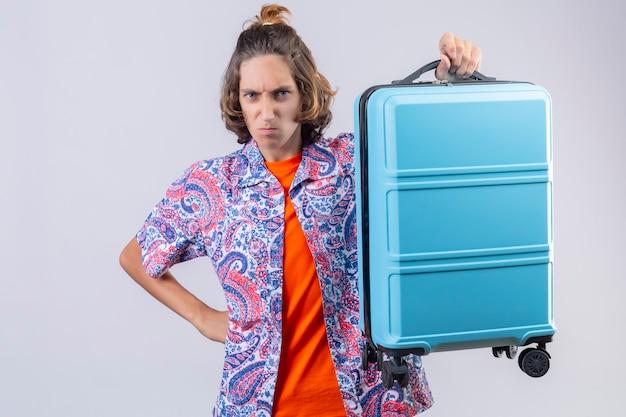 Ragazzo giovane viaggiatore bello scontento che tiene la valigia sulla spalla accigliato con rabbia in piedi Foto Gratuite