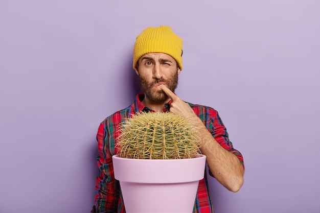 Displeased young man pricks his finger from cactus thorn, stands near potted plant, wears yellow hat Free Photo