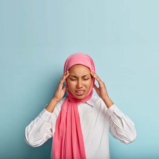 Displeased young muslim woman suffers from painful migraine, touches temples, feels intense, has strong headache, wears pink veil and white shirt Free Photo