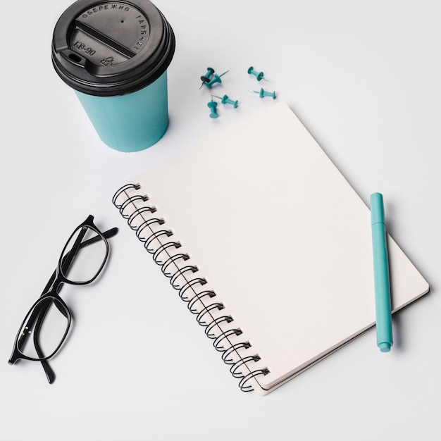 Disposable coffee cup; pen; eyeglasses; spiral notepad; thumbtack pins on white background Free Photo