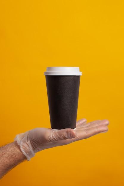 Одноразовый стаканчик, удерживаемый рукой в защитной перчатке Premium Фотографии