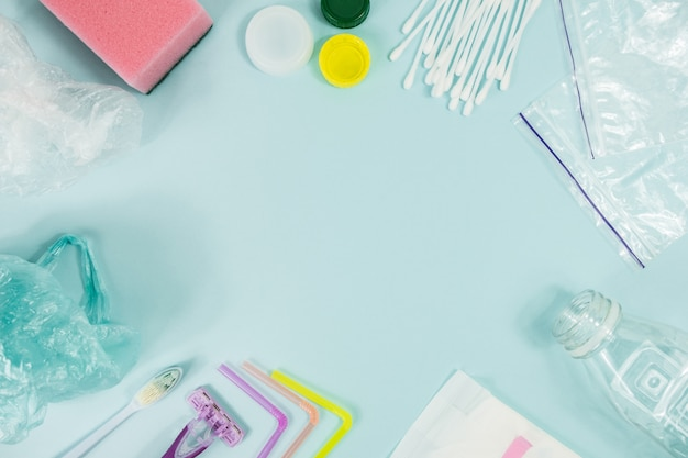 Disposable plastic items of every day use on blue background Premium Photo
