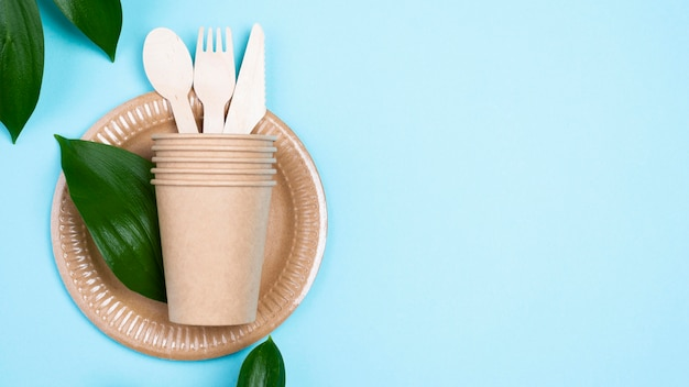 Disposable plates with cups and cutlery blue copy space background Free Photo