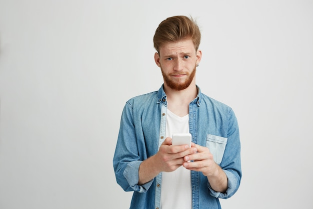 Dissapointed upset young man with beard holding smart phone looking at camera. Free Photo