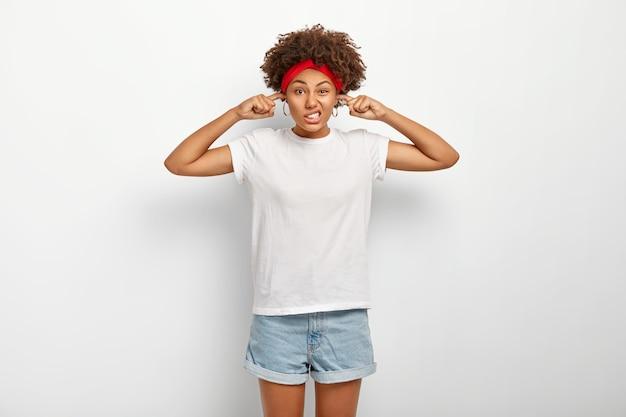 Donna afroamericana insoddisfatta incapace di concentrarsi, disturbata da un forte rumore, tappi le orecchie con le dita, aggrotta le sopracciglia e sembra infastidita, indossa abiti casual, isolato su bianco Foto Gratuite