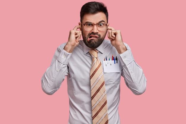 Capo maschio infastidito insoddisfatto vestito in modo formale, tappi le orecchie, non vuole sentire le lamentele dei colleghi, aggrotta la fronte per il dispiacere Foto Gratuite