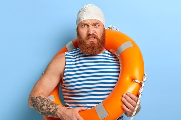 Недовольный бородатый рыжий мужчина выглядит сердито, носит резиновую белую шапочку, несет жизнь, выражает отрицательные эмоции. Бесплатные Фотографии