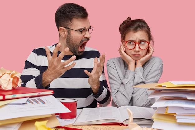 不満を持ったあごひげを生やした若い男性家庭教師のジェスチャーは、宿題の準備ができていない怠惰な研修生に怒って叫びます 無料写真