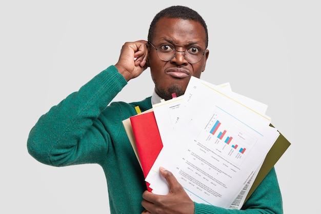 不満のある黒人男性は会計報告書を作成し、インフォグラフィック付きの書類を保持し、視力を良くするために眼鏡をかけています 無料写真