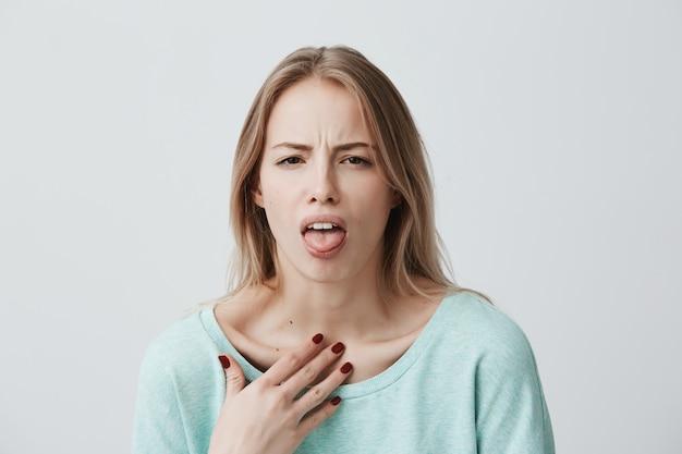 不満のある金髪の女性モデルは顔をしかめ、嫌な表情をし、舌を見せ、コンプライアンス違反を表明し、誰かにいらいらし、何かを拒否します。人と否定的な表情 無料写真