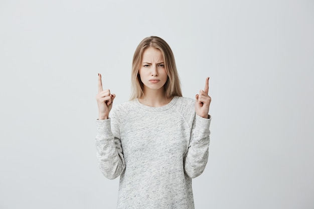 Dissatisfied blonde woman frowning face looking angrily and pointing fingers at copy space above head Free Photo