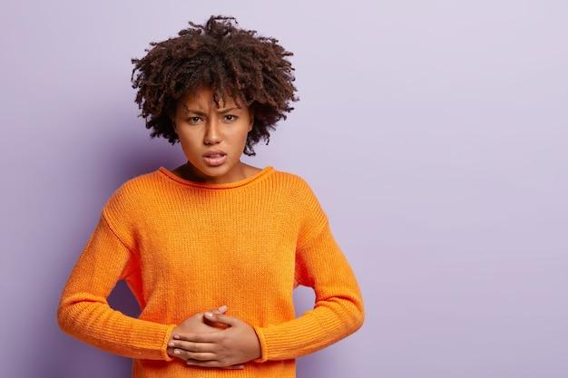 불만족스러운 어두운 피부의 여성은 손을 뱃속에 유지하고, 통증을 겪고, 월경을하고, 주황색 점퍼를 착용하고, 곱슬 머리가 있고, 보라색 벽 위에 절연되어 있으며, 광고를위한 여유 공간이 있습니다. 무료 사진