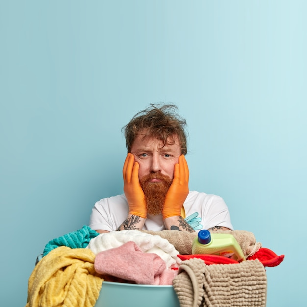 Dissatisfied desperate ginger man with messy hair, touches cheeks with both hands, overworked, has pile of dirty towels, stands over blue wall, blank space for your advertising content Free Photo