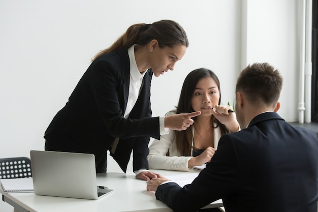 Dissatisfied female executive blaming threatening male employee at team meeting Free Photo