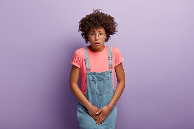 La ragazza insoddisfatta tiene le mani sull'inguine, preme il basso addome, ha un forte bisogno di servizi igienici, ha la sindrome della cistite Foto Gratuite
