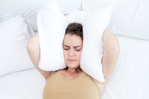 Dissatisfied lady covering ears with pillow in bed Free Photo