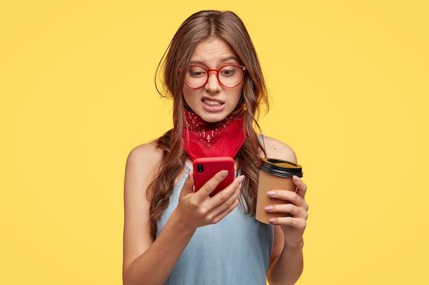 Una bella donna insoddisfatta guarda con disgusto e avversione al cellulare, modifica la foto in un'app speciale, beve caffè da asporto, posa su un muro giallo, si sente antipatica, connessa a internet ad alta velocità Foto Gratuite