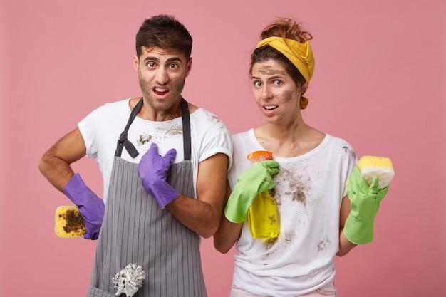 Uomo e donna insoddisfatti in vestiti sporchi che tengono la spugna e lo spruzzo di lavaggio che sono disordinati Foto Gratuite