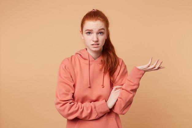 Donna dai capelli rossi insoddisfatta con una coda vestita in felpa con cappuccio con qualcuno che discute con una mano sollevata con il palmo verso l'alto cercando di dimostrare qualcosa Foto Gratuite